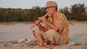Hombre mayor que toca la flauta de bambú en la playa en la puesta del sol almacen de video