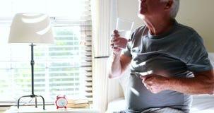 Hombre mayor que toma la medicina en el dormitorio almacen de metraje de vídeo