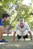Hombre mayor que trabaja con el instructor personal In Park Imagenes de archivo