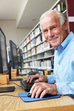 Hombre mayor que trabaja en el ordenador en biblioteca Imagen de archivo libre de regalías