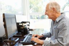 Hombre mayor que trabaja en el ordenador en el país Fotos de archivo libres de regalías
