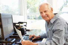 Hombre mayor que trabaja en el ordenador en el país Fotos de archivo