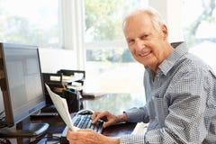 Hombre mayor que trabaja en el ordenador en el país Fotografía de archivo libre de regalías