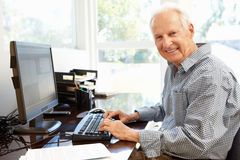 Hombre mayor que trabaja en el ordenador en el país Foto de archivo