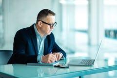 Hombre mayor que trabaja en el ordenador portátil en oficina foto de archivo libre de regalías