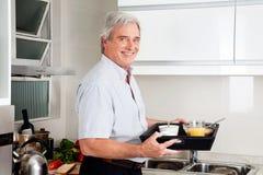 Hombre mayor que trae la bandeja del desayuno Fotos de archivo libres de regalías