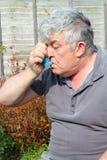 Hombre mayor que usa el inhalador. fotos de archivo libres de regalías