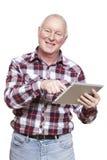 Hombre mayor que usa la sonrisa del ordenador de la tableta Imágenes de archivo libres de regalías