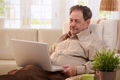 Hombre mayor que usa el ordenador en el país Foto de archivo libre de regalías
