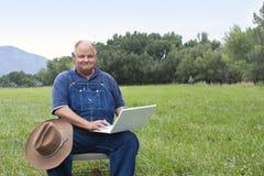 Hombre mayor que usa el ordenador portátil Fotografía de archivo libre de regalías