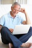 Hombre mayor que usa el ordenador portátil Foto de archivo libre de regalías