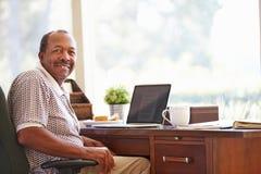 Hombre mayor que usa el ordenador portátil en el escritorio en casa imagen de archivo libre de regalías