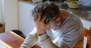 Hombre mayor que usa el ordenador portátil en la cocina en casa 4k almacen de metraje de vídeo