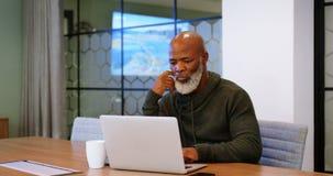 Hombre mayor que usa el ordenador portátil en la sala de conferencias 4k almacen de metraje de vídeo