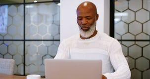 Hombre mayor que usa el ordenador portátil en la sala de conferencias 4k metrajes