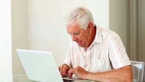 Hombre mayor que usa el ordenador portátil en la tabla almacen de video