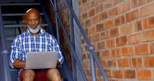 Hombre mayor que usa el ordenador portátil en las escaleras en la sala de estar 4k almacen de metraje de vídeo