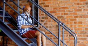 Hombre mayor que usa el ordenador portátil en las escaleras en la sala de estar 4k almacen de video