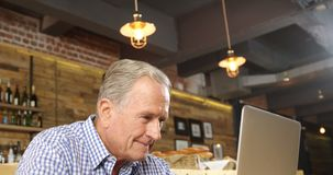 Hombre mayor que usa el ordenador portátil en el restaurante 4k metrajes