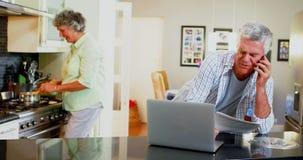 Hombre mayor que usa el ordenador portátil mientras que mujer que cocina en el fondo 4k almacen de video
