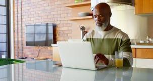 Hombre mayor que usa la cocina mínima en casa 4k del ordenador portátil almacen de video