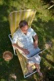 Hombre mayor que usa la computadora portátil al aire libre Fotos de archivo libres de regalías