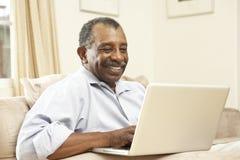 Hombre mayor que usa la computadora portátil en el país Imágenes de archivo libres de regalías