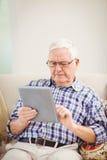 Hombre mayor que usa la tableta digital Imagen de archivo libre de regalías