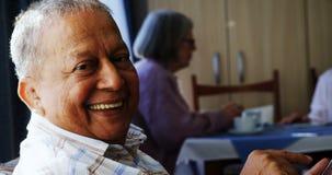Hombre mayor que usa la tableta digital con sus amigos que se sientan en el fondo 4k almacen de metraje de vídeo