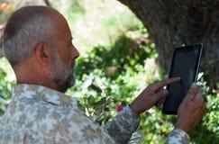 Hombre mayor que usa la tableta/el ebook mayor de la lectura del hombre fotos de archivo libres de regalías