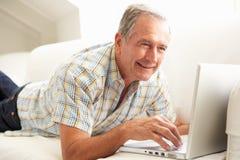 Hombre mayor que usa sentarse de relajación de la computadora portátil en el sofá Imagenes de archivo