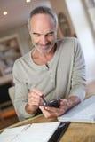 Hombre mayor que usa smartphone en casa Imágenes de archivo libres de regalías