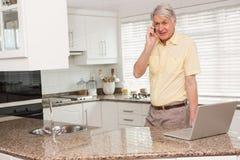 Hombre mayor que usa su ordenador portátil en el teléfono Fotos de archivo libres de regalías