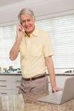 Hombre mayor que usa su ordenador portátil en el teléfono Imagen de archivo