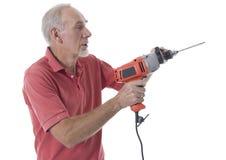 Hombre mayor que usa un taladro eléctrico Foto de archivo libre de regalías