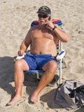 Hombre mayor que usa un teléfono celular en la playa imagenes de archivo