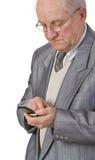 Hombre mayor que usa un teléfono móvil Fotos de archivo