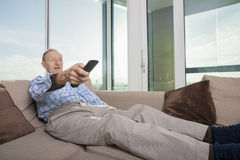 Hombre mayor que ve la TV en el sofá en casa Imágenes de archivo libres de regalías