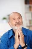 Hombre mayor religioso preocupante que ruega Foto de archivo libre de regalías