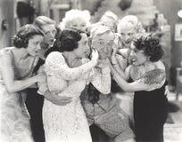 Hombre mayor rodeado por las mujeres jovenes flirtatous Imágenes de archivo libres de regalías