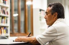 Hombre mayor serio que se sienta en un banco de la biblioteca, escribiendo en su libro imagen de archivo libre de regalías