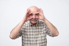 Hombre mayor soñoliento aburrido que intenta abrirse los ojos con los fingeres fotografía de archivo libre de regalías