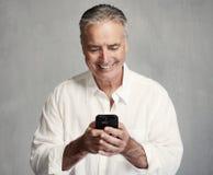 Hombre mayor sonriente con smartphone fotos de archivo