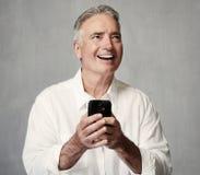 Hombre mayor sonriente con smartphone foto de archivo