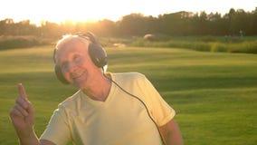 Hombre mayor sonriente en auriculares almacen de metraje de vídeo