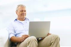 Hombre mayor sonriente en el sofá fotos de archivo