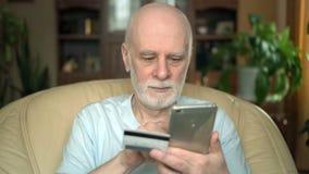 Hombre mayor sonriente hermoso que se sienta en silla en casa Compra en línea con la tarjeta de crédito en smartphone almacen de video
