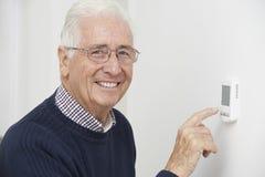 Hombre mayor sonriente que ajusta el termóstato de la calefacción central Fotos de archivo