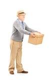 Hombre mayor sonriente que da una caja alguien Imagenes de archivo