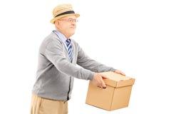 Hombre mayor sonriente que da una caja alguien Imagen de archivo libre de regalías